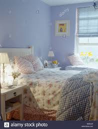 floral bedlinen and checked quilt on bed in mauve country bedroom