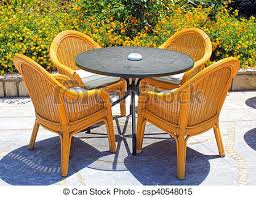 wicker patio chairs and table in the garden stock photography
