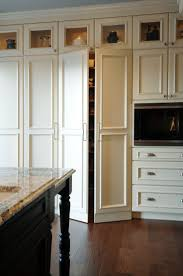 25 best kitchen pantry cabinets ideas on pinterest pantry ebony kitchen island with turned legs and granite countertops lit glass front top kitchen cabinets and oak