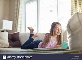 young reading book lying on sofa stock photo royalty free