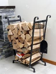 pile of firewood logs stored on metal stand next to fireplace