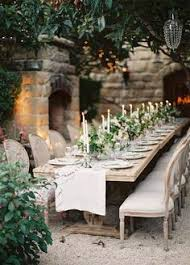 a long banquet table draped in a white textured tablecloth and