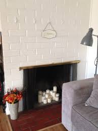 white brick fireplace with stainless steel shelf and black firebox
