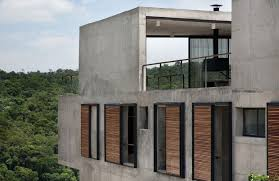 hillside house with 2 concrete volumes 2nd story entrance bridge