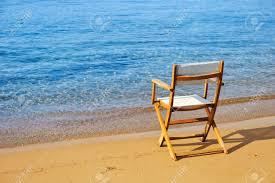 Chairs On A Beach An Empty Chair On A Golden Sandy Beach Near The Water Stock Photo