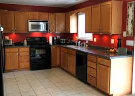 red wall color plus light brown wooden kitchen cabinet plus black
