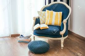 cozy armchair with open book and decorative pillows interior
