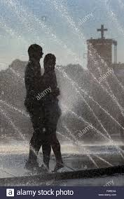 cool hoses teenagers standing in water fountains splashing from fire hoses to