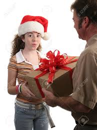 a surprised in a santa hat receiving a christmas gift from