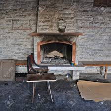 chair and table close to dirty fireplace abandoned decayed house