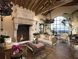 mediterranean living room with stone fireplace u0026 exposed beam in