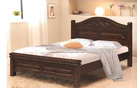 dark brown stained wooden bed frame with carved curved headboard