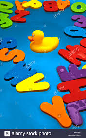 rubber duck and colorful alphabet letters floating in water in