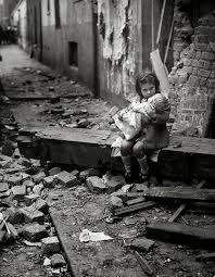 si e de una bambina con la sua bambola siede sulle macerie della propria