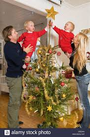 At Home Christmas Trees by Couple With Two Kids Decorating The Christmas Tree At Home Stock