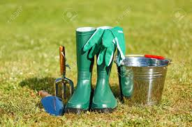 gardening equipment tiny spade rake gum boots and gloves stock