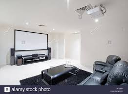 home theater room with black leather recliner chairs projector in