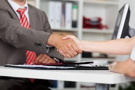Office Desk Close Up Of Businessman Shaking Hands With Female Candidate