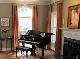 arched window treatment with orange long drapes and corner piano
