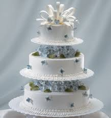 white wedding cake in three tiers with blue flowers green and