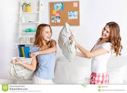 happy teen friends fighting pillows at home stock photo