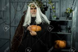 wicked old witch with white long hair and beard in black robe
