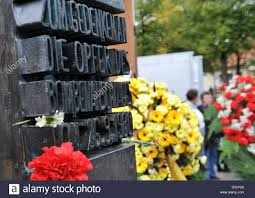 floral wreaths stand at the memorial for the victims of the stock