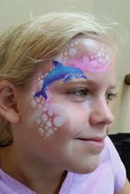 child with airbrush face painting design of a dolphin