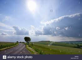 sun shining in blue sky with clouds countryside road stock
