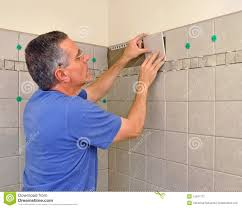 man installing ceramic tile in bathroom stock photography image