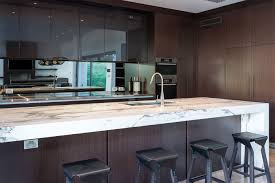 white marbled stone benchtop against dark timber cabinetry