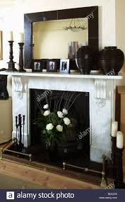 large rectangular black framed mirror on marble fireplace with