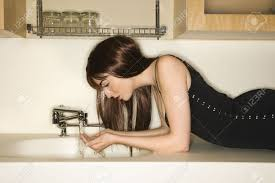 pretty caucasian young woman lying on kitchen counter drinking