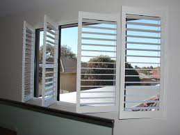 decorating plantation blinds in white with grey paint wall also