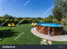 The Backyard by Above Ground Pool Sets On Concrete Stock Photo 434375476