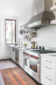 white painted exposed brick kitchen wall transitional kitchen