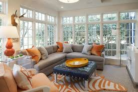 gray and orange living room features walls of undressed windows