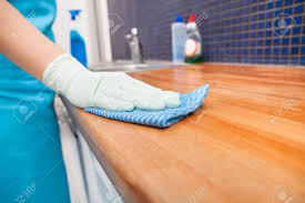 closeup of young woman wearing apron cleaning kitchen worktop