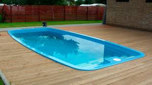 swimming pool fiberglass inground pool with small stoned wall and