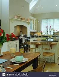 old wood table set for lunch in country kitchen extension with aga