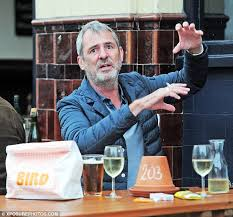 neil morrissey puts on an animated display as he enjoys a drink