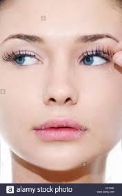 female with blue eyes applying false eyelashes andrea ciriminna