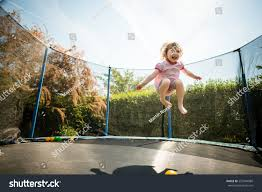 little child enjoys jumping on trampoline stock photo 557844880