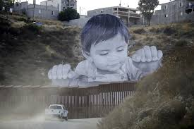 giant portrait of toddler peers over u s mexico border wall