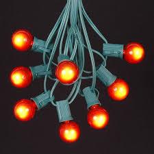orange satin g30 globe outdoor string light set on green