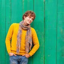 sedere di uomo uomo riccio sorridente in maglione e sciarpa gialli sulle sedere