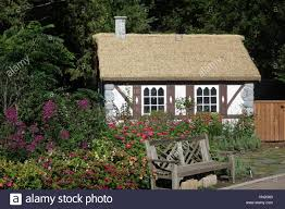 tudor style english cottage with thatch roof in garden setting