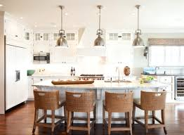 white marble kitchen island and four wicker bar stools with back