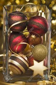 mixed ornaments in big glass vase up stock photo