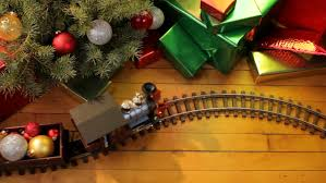 toy electric train filled with decorations passes in front of